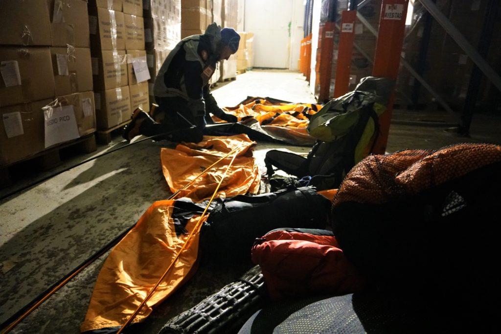 Manipulando con unos guantes finos una tienda de campaña dentro de la una cámara frigorífica a -18ºC.