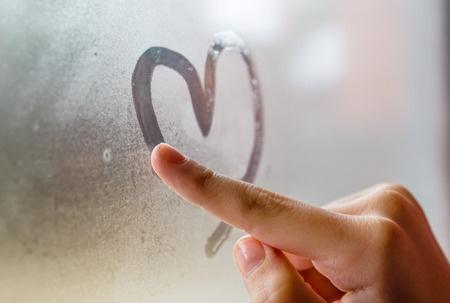 37205012 - little girl drowing heart on wet window